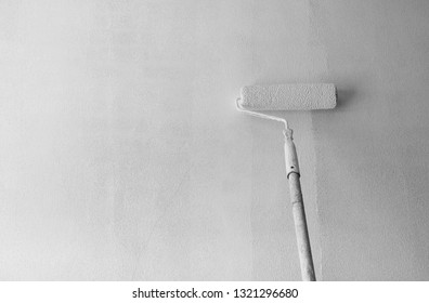 Long handle roller brush applying primer paint on white wall, building and home renovation concept