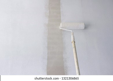 Long handle roller brush applying primer white paint on cement wall background , building and home renovation concept
