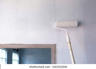 Long handle roller brush applying white primer paint on concrete wall with glass blocks in part of door frame, building and home renovation concept