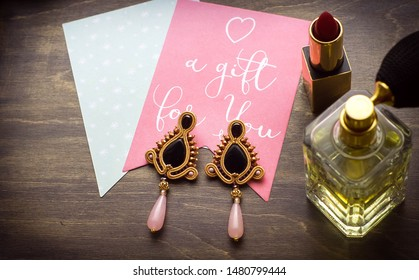 Long, hand-sewn soutache earrings, lipstick and perfume bottle in a fashionable collage