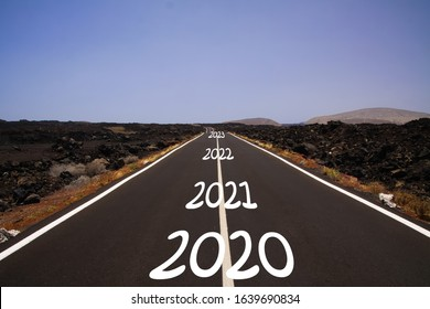 Long hard stony successful way concept: view on endless asphalt road through dry arid volcanic landscape with numbers of years 2020, 2021, 2022, 2023