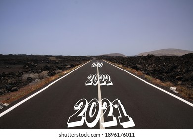 Long hard stony successful way concept: view on endless asphalt road through dry arid volcanic landscape with numbers of years 2021, 2022, 2023 (focus on first number)