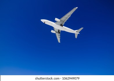 long haul widebody white passenger airplane on a blue sky background. bottom view a few seconds before landing. composition photography. flying overhead towards destination airport. travel concept.