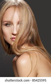 Long health hairstyle. Beauty and haircare. Sensual woman model with health and shiny dark blond hair on gray background