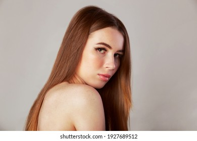 Long healthy straight hair. Beauty woman with long shiny brown hair. Model brunette portrait isolated on a gray background.