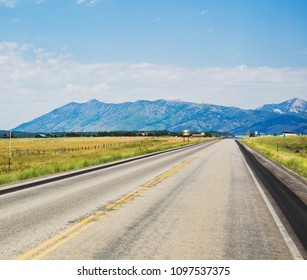 Long highway leading into distant  mountains.