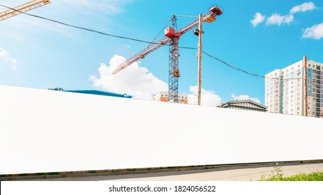 long hoarding with empty space for mock up on construction site red crane and blue sky background outside - Shutterstock ID 1824056522