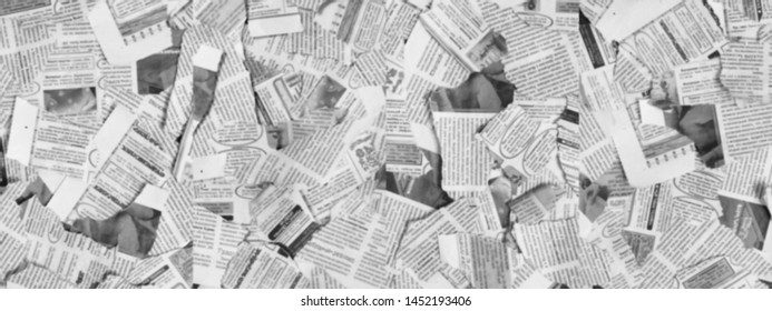 Long horizontal banner with lots of old torn newspapers on horizontal surface. Background texture, top view, blurred. Concept for news and information - could be used for web design or advertisement