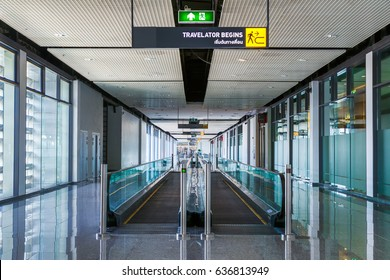 Long horizontal escalator at international airport terminal.