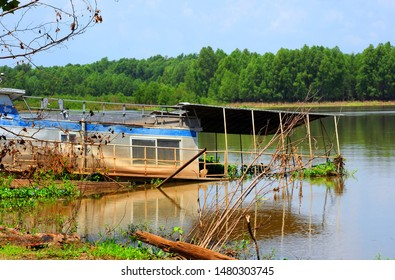 Long houseboat collapses as it sit on the Arkansas River in Arkansas.  Muddy water has stained sides of houseboat.
