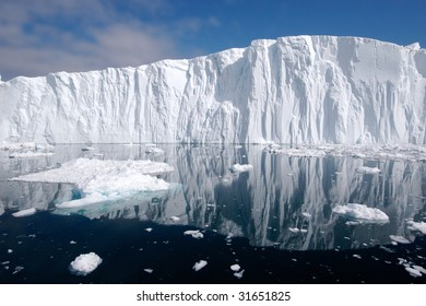 Long iceberg wall seen from distance. The Iceberg still has'nt turned around. Smaller pieces in the front.
