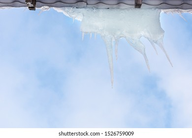 Long icicles against blue sky. Winter, icicles, ice on the roof. Icicles. Icicles hang on the roofs of house in winter.