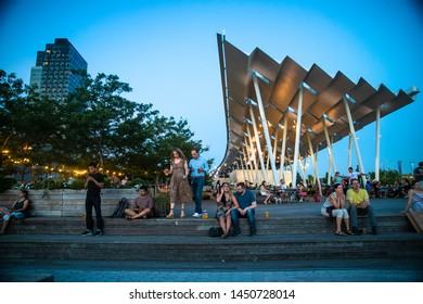 LONG ISLAND CITY, NEW YORK - JULY 13, 2019:  View at Gantry Plaza State Park on a summer evening with people visible.