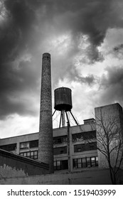 Long Island City,NY,USA 10.1.19. Black and white image a dormant smokestack and water tower with ominous clouds.