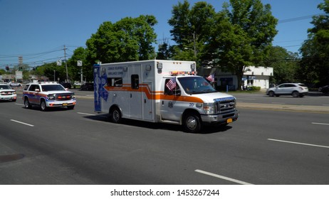 Long Island, NY - Circa 2019: Local volunteer ambulance truck drives down closed road for small town memorial day parade celebration honoring American veterans and military