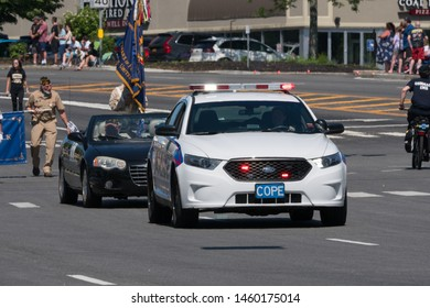 Long Island, NY, Circa 2019: Suffolk County police car leads memorial day parade celebration in local town to honor active and veteran military service men and women on beautiful summer day
