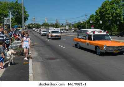 Long Island, NY - Circa 2019: Ambulance fleet drive by crowd watching Memorial Day parade through streets of small town America during summer holiday celebration