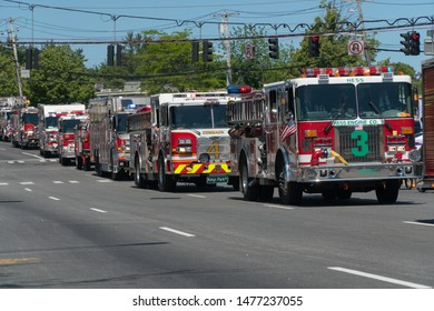 Long Island, NY - Circa 2019: Memorial day parade celebration down closed road. Spectators watch fire department truck brigade drive by with sirens and horns to honor military