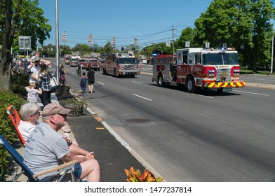 Long Island, NY - Circa 2019: Memorial day parade celebration down closed road. Spectators watch fire truck brigade drive by with sirens and horns to honor military