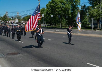 Long Island, NY - Circa 2019: Memorial day parade celebration, EMS and fire fighters march in uniform down street holding american flag to honor USA military service
