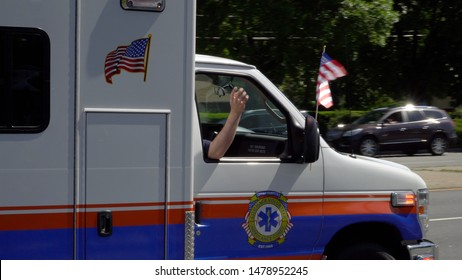 Long Island, NY - Circa 2019: Ambulance emergency vehicle close up driving in memorial day parade during bring summer day celebrate america freedom and honor military. Wave hands and flag from window