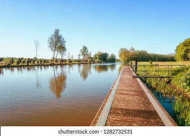 A long jetty along the river Linge in the Betuwe region in The Netherlands with a row of cut willows on the other side