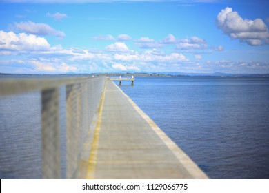 Long jetty with blue sky and white fluffy clouds