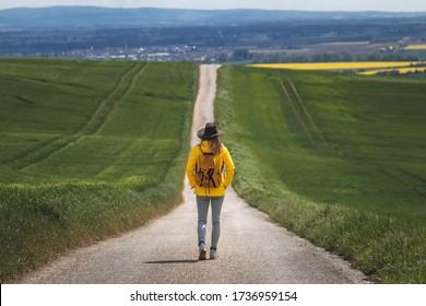 Lange Reise. Wanderfrau, die auf einer leeren Straße spaziert. Wanderer mit Hut und Rucksack mit gelber wasserfester Jacke. Reisekonzept. Alles weg