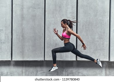 Long jump. Modern young woman in sports clothing jumping while exercising outdoors