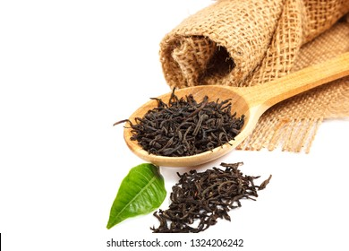 Long leaf black tea in a wooden spoon isolated on white background.