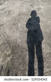 long leg shadow of a person on street cement background texture