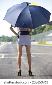 Long legged grid girl standing on the grid of a circuit, holding an umbrella