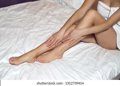 long legs of girl sitting in bed in white towel