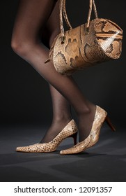 long legs in snakeskin shoes with handbag over black