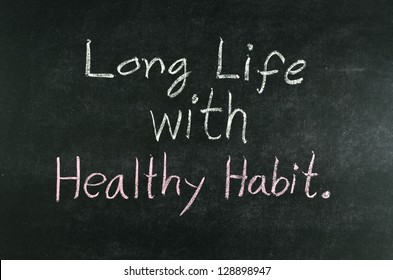 """long life with healthy habit"" word written on blackboard"