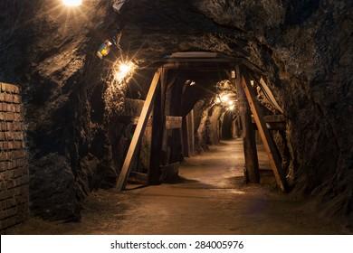 Long lighten tunnel through gypsum mine with wooden beams