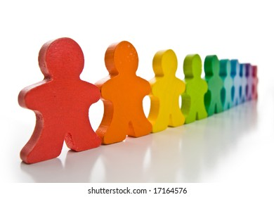 Long line of brightly colored wooden people isolated on a white background.