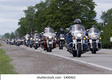 long line of motorcycles on country road