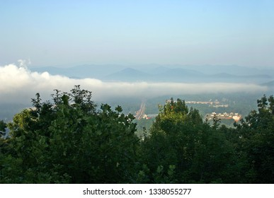 A long, low lying cloud bank hovers over a small city in the Appalachian Mountains