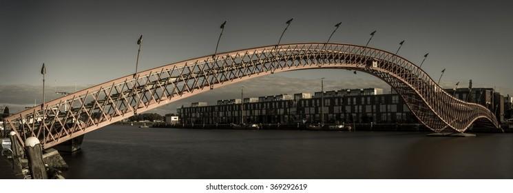 Long and modern bridge. Amsterdam, The Netherlands. Monochromatic, long exposure panorama.