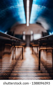 Long narrow iron stairway stretching deeper underground to a metro station as an additional way between two escalators, picturesque colors shallow depth of field, selective focus on metal steps
