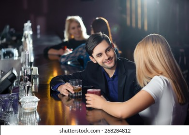 Long night. Couple joyfully interacting by the bar counter in nightclub or restaurant