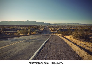 long old asphalt road Route 66 through desert and blue sky