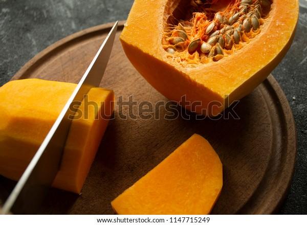 Long orange pumpkin cut into pieces on a wooden board on black background