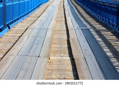 Long partially renovated wavey old wooden bridge with new blue metal frame on each side and strong support on warm sunny autumn day