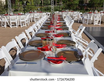Long party dinner table at an outdoor venue decorated with ivory, red and gold.