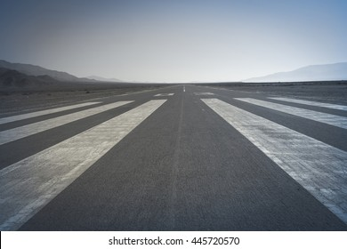 Long paved runway shot from its threshold markings