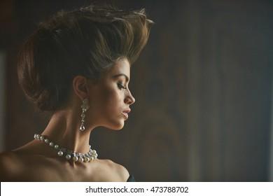 Long pearl earring hangs from an ear of beautiful model with high hair-do