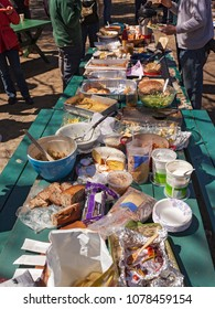 A long picnic table full of food at an outdoor picnic potluck community lunch with a few people standing around in the background.