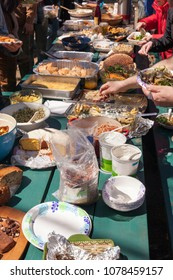A long picnic table full of food at an outdoor picnic potluck community lunch.